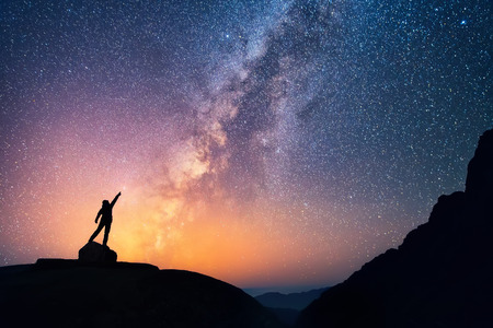 estrella: Atrapa la estrella. Una persona está de pie al lado de la Vía Láctea que señala en una estrella brillante.