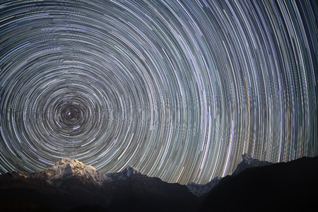 Spinning Universe. Star trails over the snowy mountains.
