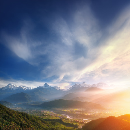 sunrise mountain: Shangri-La. Beautiful sunrise over the valley at the foothills of snowy mountains. Stock Photo