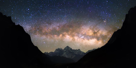 starry night sky: Bright and vivid Milky Way galaxy over the snowy mountains. Beautiful starry night sky seems to be in a bowl between the silhouetted hills.