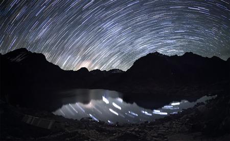 slepen van de ster over de bergen en de reflectie van de sterren in een water onder hen.