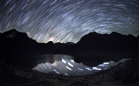 Star trails over the mountains and the reflection of the stars in a water beneath them. Stock Photo