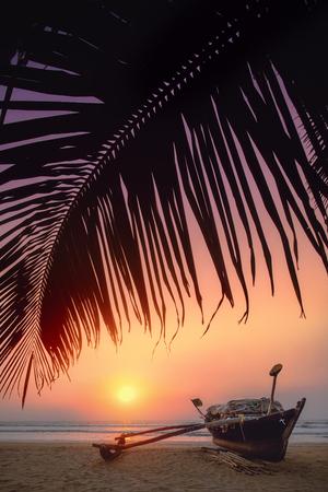 Mooie zonsondergang met een boot onder de palmbladeren op het strand.