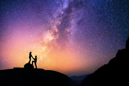 로맨틱 커플은 함께 산에 손을 잡고 서. 배경에 아름 다운 은하.