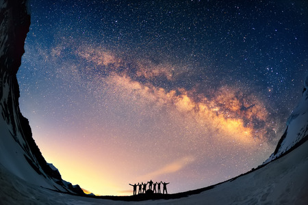 universum: Teamwork und Unterstützung. Eine Gruppe von Menschen stehen zusammen mit Händen gegen die Milchstraße in den Bergen.
