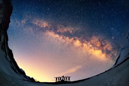 Travail d'équipe et de soutien. Un groupe de gens debout les mains tenant contre la Voie Lactée dans les montagnes. Banque d'images