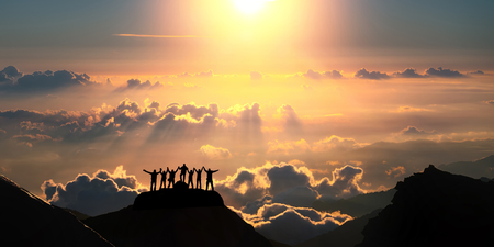 teams: On the top of the world together. A group of people stands on a hill over the beautiful cloudscape.