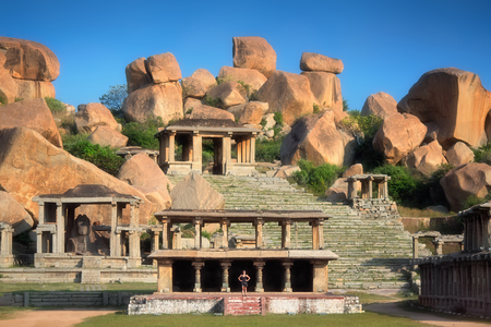 karnataka culture: Ancient temples surrounded by gigantic stones in Hampi, India. A young woman is standing inside one of them representing how huge the buildings and stones are there.
