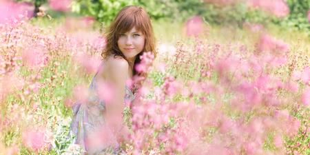 campo de flores: Pretty mujer joven está sentado en el campo rodeado de flores. Foto de archivo