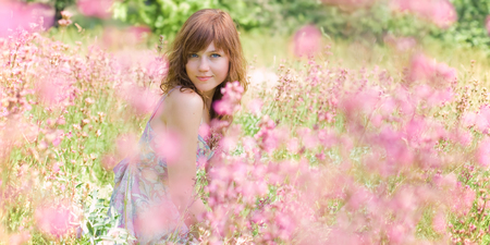 Pretty young woman is sitting in the field surrounded by flowers.