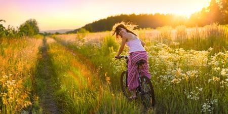 De jonge vrouw rijdt op een fiets over de zonnige veld vol bloemen.