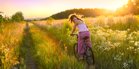 Young woman is riding a bicycle across the sunny field full of flowers.