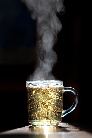A cup of hot green tea on a dark background.