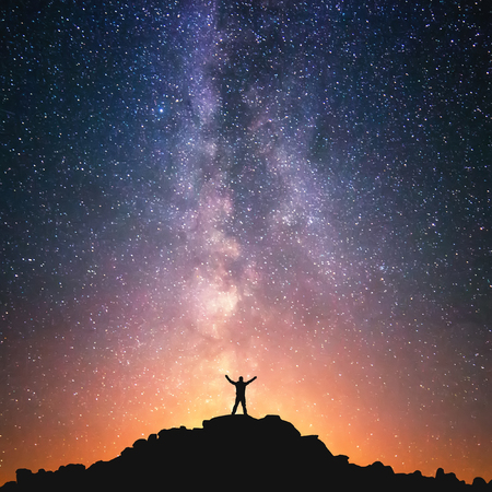 Man and the Universe. A person is standing on the top of the hill next to the Milky Way galaxy with his hands raised to the air. Stock Photo