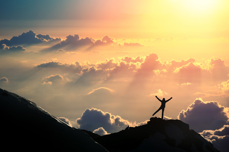 A person is standing on the top of the mountain above the clouds.