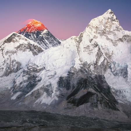 De piek van de hoogste berg ter wereld - Mt. Everest op de zonsondergang vanaf de linkerkant. En Nuptse piek 7861 m aan de rechterkant.