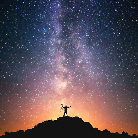 persona de pie: El Hombre y el Universo. Una persona est� de pie en la cima de la colina al lado de la V�a L�ctea con un tr�pode en sus manos. Foto de archivo