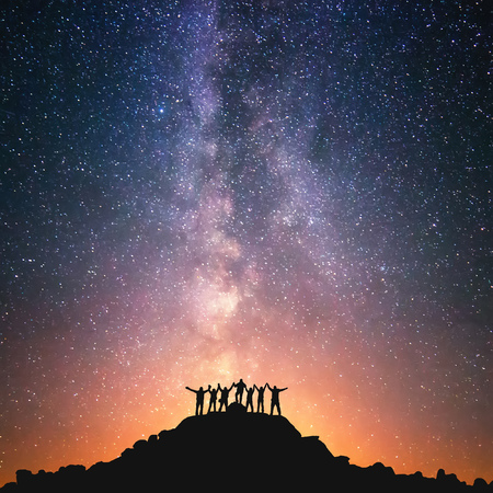 Together we stand. A group of people are standing on the top of the hill next to the Milky Way galaxy holding hands. Stock Photo