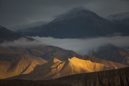 Golden Hills. Beautiful natural scenery. Hills brightly lit by the sunlight with dramatic mountain view on the backside. Captured in Upper Mustang region, Himalayas, Nepal. Stock Photo