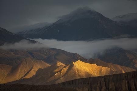 Golden Hills. Prachtige natuur. Hills fel verlicht door de zon met dramatische uitzicht op de bergen aan de achterzijde. Gevangen in Upper Mustang regio, Himalaya, Nepal. Stockfoto