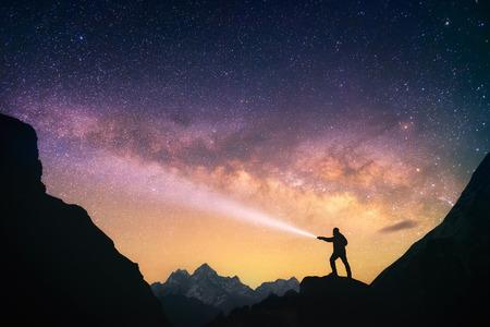 Silhouette des Mannes, die gegen die Milchstraße in den Bergen mit einer Taschenlampe in den Händen. Nepal, Everest-Region, Blick auf den Berg Thamserku 6608 m von Thame Dorf 3750 m.