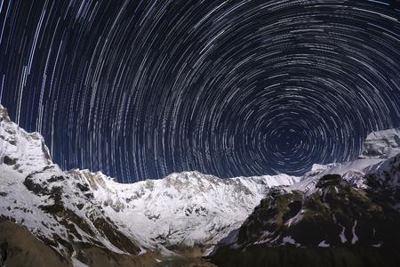 雪に覆われた山々 の峰の上のスター トレイル。ネパール、アンナプルナ地域、アンナプルナ アンナプルナ ベース キャンプから。