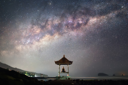 A man is sitting in meditation pose in front of the Milky Way in the night.