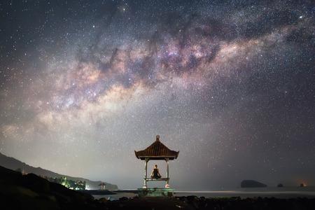 Een man zit in meditatie houding in de voorkant van de Melkweg in de nacht.