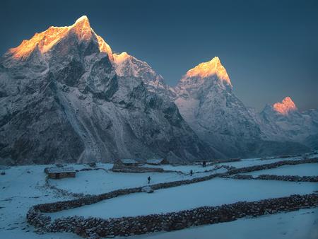 Trekkers lopen door de besneeuwde weide. Nepal, Everest regio, Dusa dorp. Van links naar rechts: Taboche Peak, Cholatse, Arakam Tse en Lobuche East.