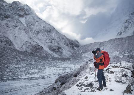 De man staat met camera in een prachtige bergvallei die foto's maakt.
