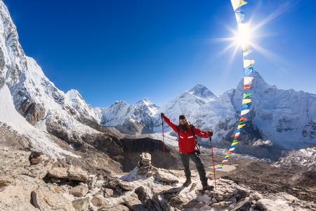 男は美しいパノラマのマウンテン ビューの前に山の頂上に立っています。ネパール、エベレスト地域、エベレスト カラパタール ピークからの眺め