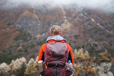 Jonge vrouw wandelaar met rugzak permanent in de voorkant van de prachtige vallei genieten van het uitzicht. Stockfoto