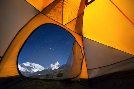 Uitzicht op de bergen van een toeristische tent. Vanuit het raam van de tent van links naar rechts zijn er twee achtduizenders - Mt. Everest (8848 m), Lhotse (8516 m) en de Ama Dablam (6814 m). Stockfoto - 56271678