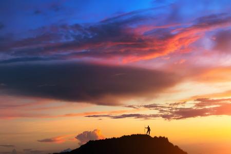 Boven aan de wereld. Een persoon staat op de heuvel onder kleurrijke hemel bij de zonsondergang. Klikte op de top van de vulkaan Batur (Bali, Indonesië).