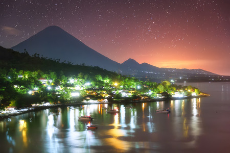 Colorful Amed harbor in the night and the highest point of the island, Agung volcano (3,142 m) is visible on the background.