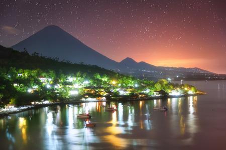 Kleurrijke haven Amed in de nacht en het hoogste punt van het eiland, Agung vulkaan (3142 m) is zichtbaar op de achtergrond.