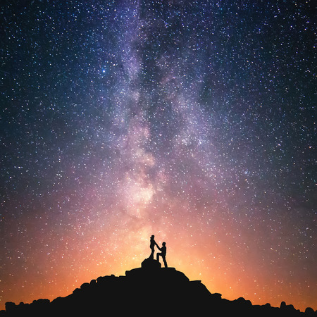 Romantic couple standing together holding hands in the mountains. Beautiful Milky Way galaxy on the background.
