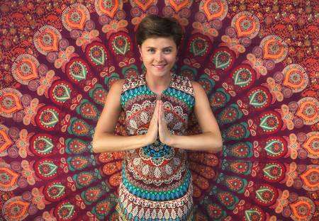 Namaste greeting. Cheerful young woman on a bright background. Stock Photo