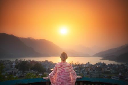 明るい未来。成熟した女性は、湖と山脈の美しい夕日を眺めながらテラスに立っています。