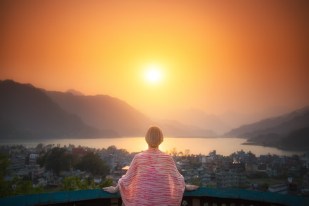 Bright future. Mature woman is standing on the terrace looking at the beautiful sunset over the lake and mountains. Stock Photo