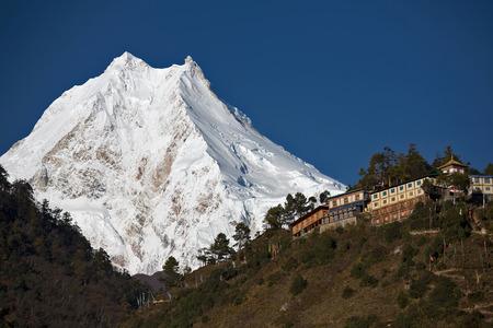Himalaya-boeddhistische klooster voor Manaslu Peak (8.156 m) - de achtste hoogste berg ter wereld. Stockfoto - 71980260