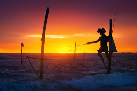 Sri Lanka's Stilt Fisherman. Vissen op stilt is heel gebruikelijk in veel Aziatische landen, maar vooral - in Sri Lanka, in het dorp Ahangama. Stockfoto - 81999976