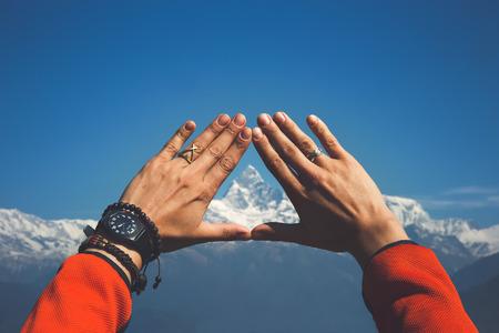 Handen die de sneeuwbergpiek ontwerpen. Mt. Machapuchare (6.993 m) in het centrum (Nepal, Himalaya).