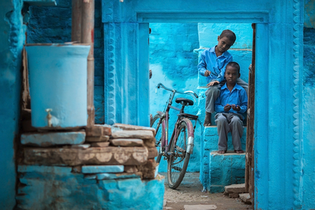 VARANASIINDIA - NOVEMBER 2012 - Two Indian school boys are sitting in the yard of their house in Varanasi, India in November 2012. Editorial