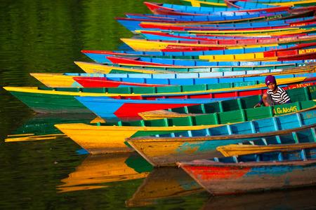 Kleurrijke ligplaats. Heldere en kleurrijke boten die zich in één ruw op het water bevinden. Een boatman (jonge nepali jongen) zit in een van hen. Stockfoto - 82710720