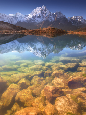 Nepal, Manaslu Region, a reflection in the Bimtang lake (3,680 m) of the Phungi peak (6,538 m) in the centre and the Mansiri Himal (7,059 m) at the left side. Stock Photo