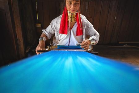 YWAMA VILLAGE  MYANMAR - FEBRUARI 2014 - Een vrouw uit de Padaung-stam, gewoonlijk de Long Neck-stam genoemd, weven in februari 2014 in Ywama, Inle Lake, Myanmar.