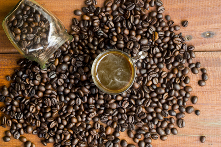 Hot espresso and coffee beans in glass jar on wooden board background.