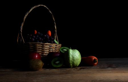 Still Life, pile of fruits and basket on the old wooden table. Stock fotó