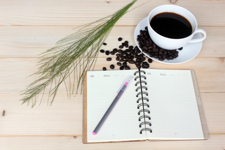 Hot Coffee and beans with Notebook on  wooden board. Stock fotó